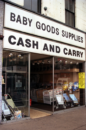 "A terraced shopfront with full-length glass windows and a recessed entrance in the middle. Cots and pushchairs are displayed in the windows, and a sign above reads ""Baby Goods Supplies / Cash And Carry""."