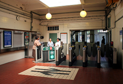 The interior of a small station ticket hall, with a British Rail symbol mosaic on the tiled floor. Three people are standing together at the left of the photo, on different sides of the ticket gates. Globe lights hang from the ceiling. The ticket window in the wall to the left of the ticket gates has the shutter pulled down. Daylight is visible through windows beyond the ticket gates.