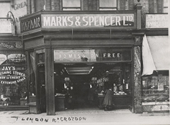 "A black-and-white photo showing a small shopfront with signs above it reading ""Bazaar"", ""Marks & Spencer Ltd"", and ""Admission Free"". A few shoppers and shop assistants are looking out of the open shopfront towards the camera. The shopfront protrudes slightly from the shop to its left, giving a diagonal aspect to the side of the shop. Writing is visible on the window of the shop to the left: ""Jay's Furnishing Stores Ltd. Cash or credit. Extensive stock."""