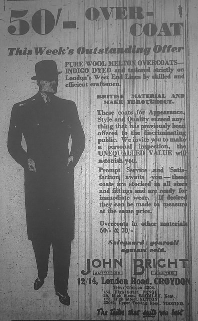 "An advertisement headed ""50'- over-coat / This Week's Outstandind Offer"".  A drawing of a man in a bowler hat and long, narrow coat is on the left-hand side.  At the bottom is the address ""12/14, London Road, Croydon""."
