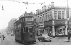A black-and-white photo showing an old-fashioned overhead-powered tram in the middle of a street.  A corner building on the right has frontages for John Hood Ltd dyers and cleaners, and the Ministry of Labour & National Service Combined Recruiting Centre and Medical Boards.