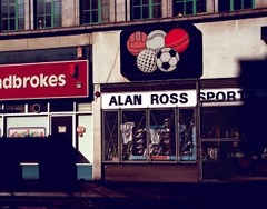 "Two neighbouring shopfronts viewed in late-afternoon sunlight with heavy shadows. The left one has a frontage sign (partially cut off) reading ""Ladbrokes"" and the right one has a sign reading ""Alan Ross Sport[s?]"". Another sign above the Alan Ross one shows a drawing of five balls — basketball (or possibly old-style football), tennis, cricket, golf, and football — arranged like the Olympic rings, with three above and two below. This shopfront has shoes and clothes visible in the window, covered by a protective metal mesh."