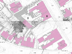 An extract from a map showing buildings on either side of a road. Some of the buildings have been coloured pink and others have been coloured grey.