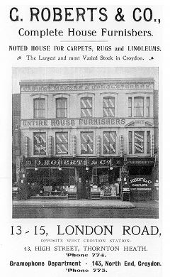 "A black-and-white advert showing an illustration of a three-storey double shopfront. The bottom of the image looks photorealistic, but the upper floors appear more like a drawing. Text above the image reads: ""G. Roberts & Co., Complete House Furnishers. Noted house for carpets, rugs and linoleums. The Largest and most Varied Stock in Croydon."". Text below the image reads: ""13-15 London Road, opposite West Croydon Station. 43, High Street, Thornton Heath. 'Phone 774. Gramophone Department - 143, North End, Croydon. 'Phone 773."""