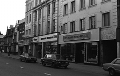 "A black-and-white photo of an oblique view onto a row of shops of varying architectural styles. The bulk of the picture is taken up by a tall building in the foreground. The closest shop has a sign reading ""Lee's House Furnishers Ltd"". An opening next to this leads into an alley with a bas-relief sign above it reading ""REMOVALS"" on a curved baseline over a simple abstract design."