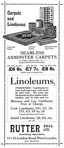 "A tall, narrow black-and-white advert with a drawing of several carpets (rolled up and laid out flat) at the top. Text advertises ""Carpets and Linoleums"", ""Seamless Axminster Carpets"", and ""we Measure and Lay Linoleums Free of Charge."" A decorative border is around the whole."