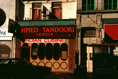 "A small restaurant frontage in the middle of a terrace. Much of the image is in shadow. A sign above the restaurant reads ""Ahmed Tandoori / Croydon"" in orange letters on a brown background, and below it a banner reads ""Indian Cuisine"" in the same orange on a white background. The front of the restaurant is tiled with small light brown tiles, and a window is set into it formed of five tall narrow ovals attached at their long sides. Five circles along the base of the wall line up with the curves of the ovals."