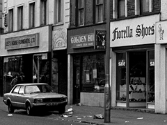 A black-and-white photo of three terraced shopfronts. A car is parked outside one of the shops, and the pavement is badly littered.