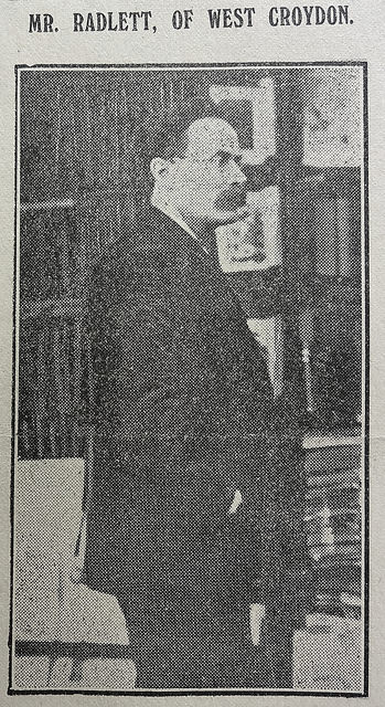 A black-and-white photo of a white man with a moustache, dark hair, and a receding hairline.  He is wearing a dark coat and standing side-on to the camera.  Shelves of books can be seen in the background.