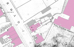 An extract from a map showing buildings and fields on either side of a road. Some of the buildings have been coloured pink and others have been coloured grey.