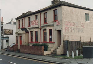 "A two-storey building with three pairs of windows along the upper floor. The outside has been painted white, but there are clear signs of weathering. The windowframes and doors are painted red. Two signs on the frontage read ""Andress Printing"". A painted sign on the side of the building shows the same text, but has worn away with time. The side of the Wandle Arms pub is visible to the left."