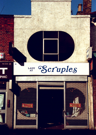 "A narrow terraced two-storey shopfront. A striking oval window is set into the first floor, and the roof profile features a large sticking-up rectangular detail. The shopfront on the ground floor has an open door-shaped space in the middle, with grid-style shutters drawn down on either side. A sign above reads ""Lady at Scruples"", with the ""Lady at"" part in smaller text than the ""Scruples""."