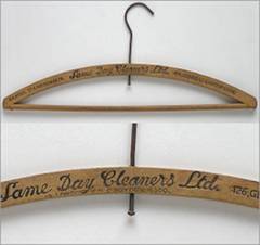 "Two pictures of the same wooden coat hanger, which has ""Same Day Cleaners Ltd"" stamped into the middle of it.  One of the pictures shows the full item and the other is a close-up on the name of the business.  Two addresses are also stamped into the coat hanger on either side of this."