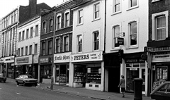 "A black-and-white photo of a terrace of shops. In the middle is one with a sign reading ""Peters Master Bakers""."