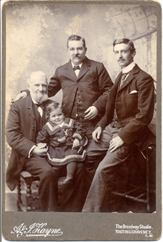 A sepia photo showing three white men and a white toddler, all with some facial resemblance. The oldest man is seated on the left; he has white hair and a white beard, and the toddler is on his lap wearing a sailor suit. The other men have short dark hair and moustaches.