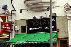"Close-up on a sign and canopy over a shopfront. The sign reads ""Papa's Ristorante Italiano"" and the canopy reads ""Papa's Dine & Dance Downstairs""."
