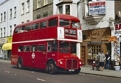 "A red double decker bus alongside a three-storey terrace with shops and restaurants on the ground floor.  To the side of the bus is a brick-fronted restaurant with multi-paned windows and a sign reading ""Pino's Place""."