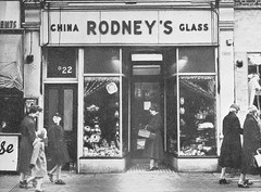 "A black-and-white photo tightly focused on a small shopfront with a central recessed doorway and windows on either side.  Several people are walking past and one is standing in the doorway.  A sign above reads ""Rodney's"" in the centre with ""China"" and ""Glass"" to either side."
