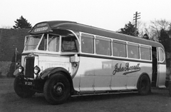 "A black-and-white photo of a coach with windows all along the side and a sliding door at the back. The blind at the front reads ""CROYDON"". ""John Bennett"" is printed on the side of the coach in a cursive font."