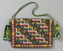 A rectangular purse decorated with counted-thread embroidery in red, yellow, orange, green, and light brown. A tasselled cord in shades of green is attached to the top at both sides.