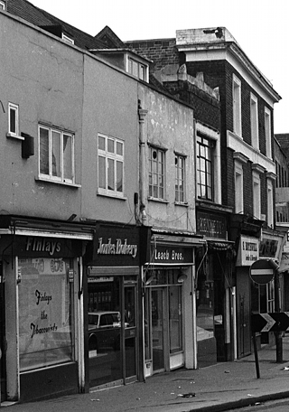 A black-and-white photo of terraced shops in varying architectural styles. The three shops on the left — Finlays, Clarks Bakery, and Leach Bros — are boxy and plain, while their neighbours to the right are more ornate.