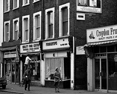 "A terrace of shops with frontages reading Post Office, Quality Food Centre, Fingertips, and ""Croydon Fru[...] / Quality Fruits & Ve[...]"". A net curtain hangs in the window of Fingertips. In front of the Quality Food Centre, a person is standing on a short stepladder doing something with the window display. Two older people are walking along the pavement."