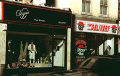 "Two terraced shopfronts next to each other. The left-hand one has a sign above reading ""Clique"" and in smaller text ""Pour Homme"", in silver writing on a black background with a thin red border.  In the shop window are three mannequins.  The right-hand one has a sign above with two Pizza Hut logos at each side and the word ""Delivery"" in the middle."