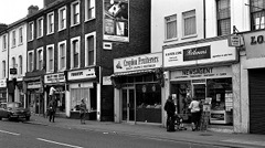 A black-and-white photo of a terraced street, with shopfronts all along the ground level including Quality Food Centre, Fingertips, Croydon Fruiterers, and N B Patel & Sons newsagent.  A few people are walking down the street and standing in front of the newsagent.  A large cigarette advert is visible on a side wall.