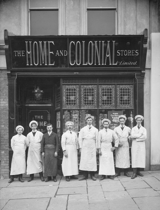 A black-and-white photo of a small shop with 'The Home & Colonial Stores' in metallic letters on a black frontage.  Eight men are standing outside; seven of them in white overalls and one in dark overalls.