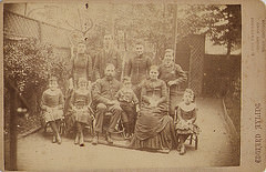 A sepia-toned photo showing a large family posing in the back garden of their home.  The parents are in their late 40s to early 50s, and the children range in age from about 4 to adult.