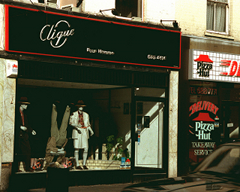 "A terraced shopfront with a sign above reading ""Clique"" and in smaller text ""Pour Homme"", in silver writing on a black background with a thin red border.  In the shop window are three mannequins.  The left-hand one is standing up with a dark suit and hat on.  The middle one is upside down and wearing a light greyish suit.  The right-hand one is wearing a light-coloured skirt suit and a hat similar to the one on the first mannequin.  To the right of this shopfront, part of a Pizza Hut shopfront is visible."