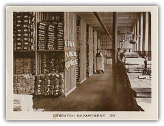 "A landscape-oriented card showing a sepia photo of a wide corridor in a warehouse.  To the left are shelves stacked with wrapped bundles, twice the height of the person standing next to them.  To the right are two more people working with folded fabric on a wide long workbench.  Below the photo is printed ""DESPATCH DEPARTMENT 30""."