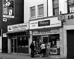 "A black-and-white photo showing two small shopfronts: Croydon Fruiterers (""Quality Fruits & Vegetables"") on the left and N B Patel & Sons tobacconist, confectioner, and newsagent on the right. The frontage of Patels bears the words ""Rothmans King Size"" in large letters.  The wall to the left of Croydon Fruiterers has a large advert for Embassy Number 1 cigarettes."