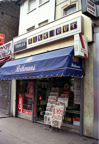A small terraced shopfront with a rack of newspapers on the pavement just outside. Decals on the windows advertise Coke, a blue canopy advertises Rothmans cigarettes, a projecting sign advertises Embassy Number 1 cigarettes, and a sign above the frontage advertises Silk Cut cigarettes.