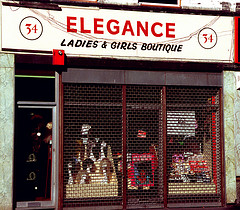 "A terraced shopfront with a mesh-style shutter down over the front.  The sign above the frontage reads ""Elegance Ladies & Girls Boutique"".  Through the mesh, some mannequin heads with wigs on are visible."