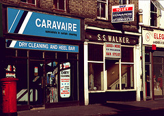 "Two terraced shopfronts, both with large front windows and signs above.  The left-hand shop has a light blue sign reading ""Caravaire / specialists in curtain cleaning / DRY CLEANING AND HEEL BAR"" above the frontage and a poster in the window reading ""2 hr dry cleaning / Saturdays included / plus first class shoe repairs"".  The right-hand shop has a rather more old-fashioned sign reading ""S. S. Walker."" above the frontage and another sign above the central door reading ""Ladies & mens / S S Walker / Hair stylist"".  The right-hand shop also has a projecting estate agent's sign higher up, reading ""Shop to let / Stuart Edwards & Partners / 102/4 High St Croydon / 01688 8313"".  A small slice of another shop can just be seen at right of frame, with the number ""34"" and the words ""ELEG... / Ladies & G...""."