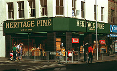 "A corner view of a double shopfront with a sign above the frontage reading ""HERITAGE PINE"" in gold letters on a dark green background.  Pine furniture is visible in the windows, as are signs reading ""SALE"" in white letters on a red background.  A few people are walking past the shop along the pavement.  The corner of the pavement is separated from the road by metal railings, on which is a sign reading ""Oakfield Road""."