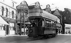 "An old-fashioned tram running in front of a parade of shops.  On the left is a frontage reading ""Bowditch & Grant"", and to the right of this is another reading ""The Creamery"" with ""Luncheons / Teas"" below.  The tram itself carries advertising for Whitbread's ale, stout, and IPA."