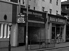 "A black-and-white photo of a terrace of shops.  The one in the middle has a sign reading ""MA[something]BRO FASHIONS"" and whitewashed windows.  A rather fashionable-looking person is walking past the next-door shop (House of Ceramics)."