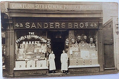 "A black and white photo of a terraced shopfront with a fully glazed frontage and two people in overalls standing on either side of the recessed central doorway.  Signs above the shopfront read: ""Corn Flour Seed & General Produce Merchant / 43 Sanders Bros 43"".  Writing on the left-hand window reads: ""The peoples corn & flour market""."