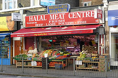 "A terraced shopfront with a display of colourful vegetables at the front.  Signs above read ""Wholesale & Retail Meat & Poultry"" and ""Halal Meat Centre / Fresh Beef * Lamb * Poultry * Fish""."