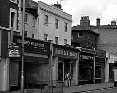 A black-and-white photo showing four shopfronts: Ma[...]bro Fashions, House of Ceramics, Fininley Ltd, and Maloneys.  House of Ceramics has an unusual shopfront with patterned tiles surrounding the windows.  A pedestrian is walking past the front of this shop.