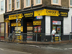 "A corner shopfront property with signs for ""Albemarle & Bond / Cheque & Pawn / Cheques Cashed / Pawnbroker"".  Railings separate the pavement from the street, and a sign on the side of these reads ""Oakfield Road""."