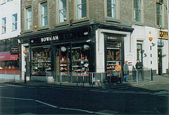 "A corner property viewed from the opposite corner of the crossroads.  The frontage on the ground floor is painted black and has a sign reading ""Bowman"" along with street numbers 60 and 62.  The windows are filled with various items.  Three people are walking past the shop.  Metal fencing runs along the road side of the pavement, and Belisha beacons stand on both sides of the shop."
