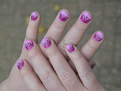 A light-skinned person's hands held crossed one over the other.  The fingernails are short and have been painted with flame-like designs in pink and magenta.