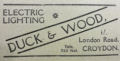 "A black-and-white newspaper advert reading: ""Electric Lighting / Duck & Wood / 47, London Road, Croydon."""