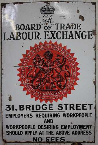 "A rectangular metal sign, portrait orientation, painted white with a large circular red ""seal"" in the middle and a stylised crown with the monogram ""GVR"" [George V Rex] at the top.  Words in black letters read: ""Board of Trade Labour Exchange / 31, Bridge Street / Employers requiring workpeople and workpeople desiring employment should apply at the above address / No fees"""