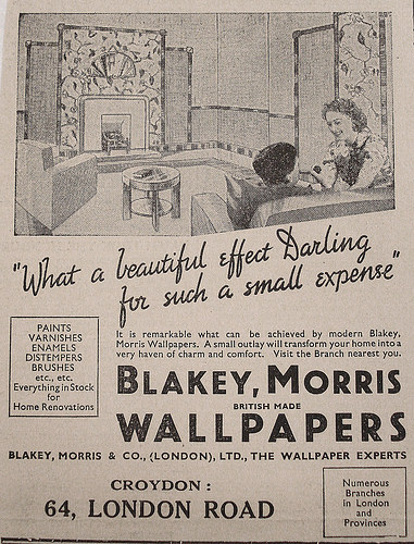 "A newspaper advertisement for ""Blakey, Morris British Made Wallpapers"" at 64 London Road, Croydon.  A line drawing at the top shows two people talking in a living room with striking patterned wallpaper, with cursive letters underneath reading ""What a beautiful effect Darling for such a small expense""."