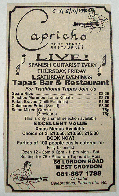 "A newspaper advertisement headed: ""Capricho Continental Restaurant / Live! Spanish guitarist every Thursday, Friday & Saturday evenings / Tapas Bar & Restaurant"".  Some sample menu prices are given, including spare ribs at £2.25, patas bravas (chilli potatoes) at £1.90, and calamares fritos (squid) at £3. Line drawings of the Spanish guitarist are included in the top-right and bottom-left corners.  Someone has written ""C.A. 5/10/1990"" in ink at the top of the clipping."
