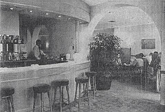 A grainy black-and-white newspaper photo of a restaurant interior.  To the left is a rounded bar with a barman behind and bar stools drawn up in front.  A large arch to the right leads through to a dining area with several seated parties.  The decor appears to be light and bright.